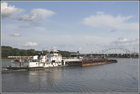A large, white tow boat pushes a raft of barges downstream on the Mississippi River under blue sky and white, puffy clouds. A large bridge is in the distance.
