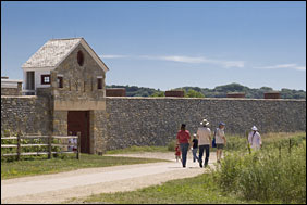 Visitors approach the gate of a historic stone fort.
