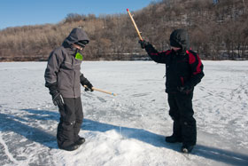 Two boys ice fishing on a snow-covered lake flanked by forested hillsides.