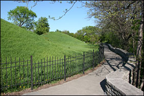 Grass-covered mounds on left are Native American gravesites. A path leads to the right between the mounds and the river bluffs.