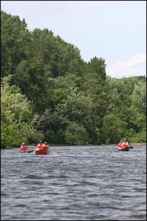 Canoeists paddle down the Mississippi River. Tree-lined bluffs tower in the background.
