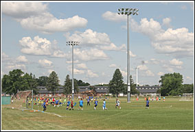 Children playing soccer on an athletic field.