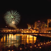 A fireworks display at night in downtown St. Paul reflected in the Mississippi River.