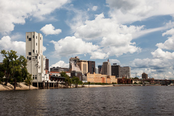 Clouds float in a blue sky over the Mississippi River in downtown Saint Paul, MN.