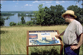 A man reads an interpretive sign that overlooks an island-dotted Mississippi River.