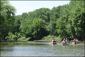 Canoeists paddle downriver amidst tree-lined banks.