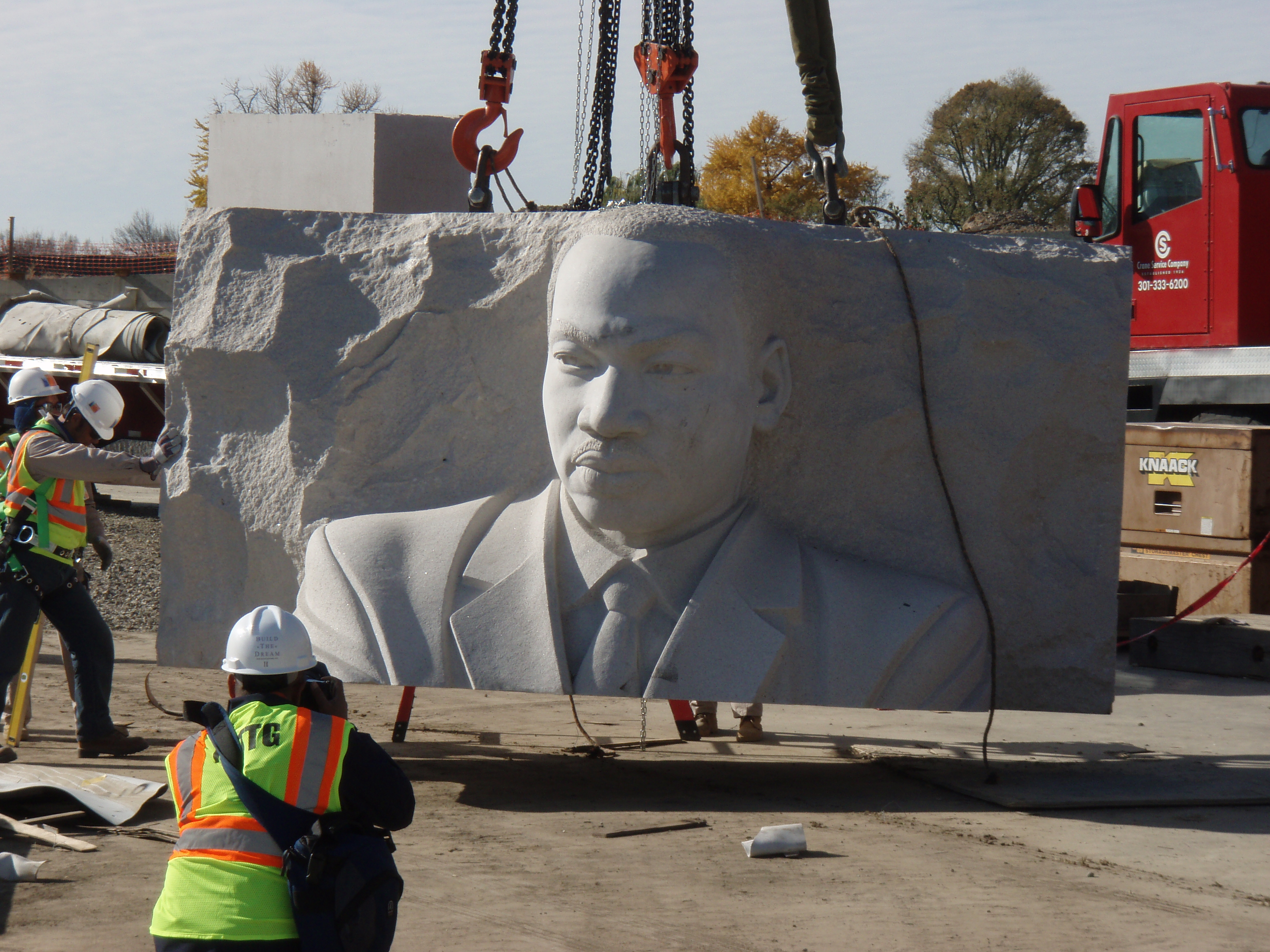 A granite slab with MLK's likeness is lifted by crane