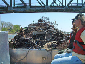 NPS boat brings volunteers and their collected junk under the Meridian Bridge at Yankton.