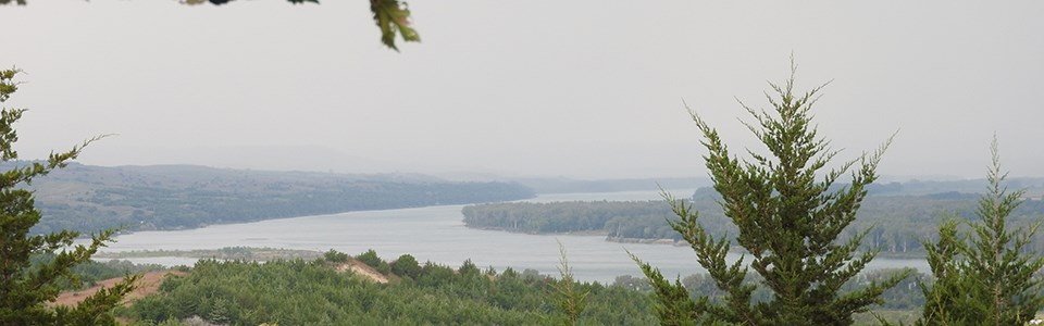 View above a river valley of eastern red cedars and the Missouri River in the background.