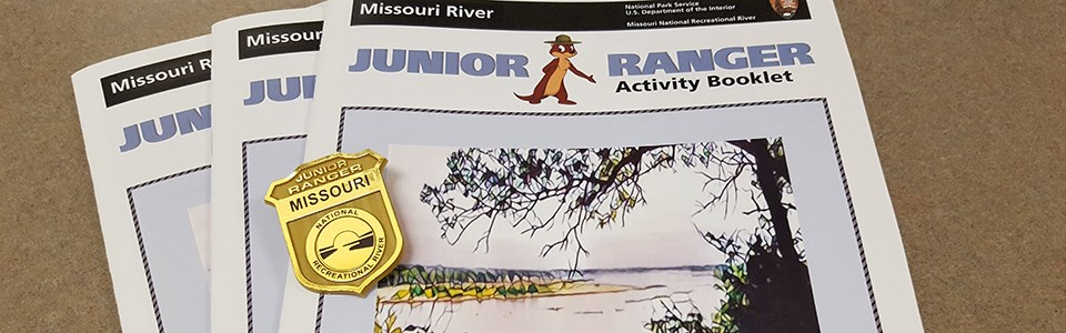 Cover view of three junior ranger booklets with a gold junior ranger badge.