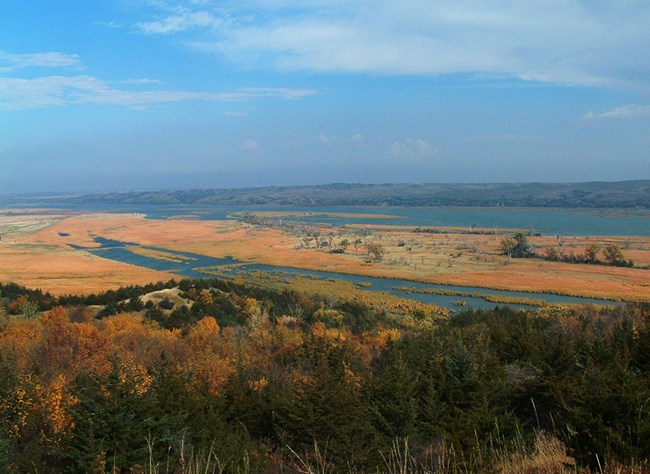 Orange, green, brown, and blue colors make up this autumn picture of the Missouri river from high above an overlook.