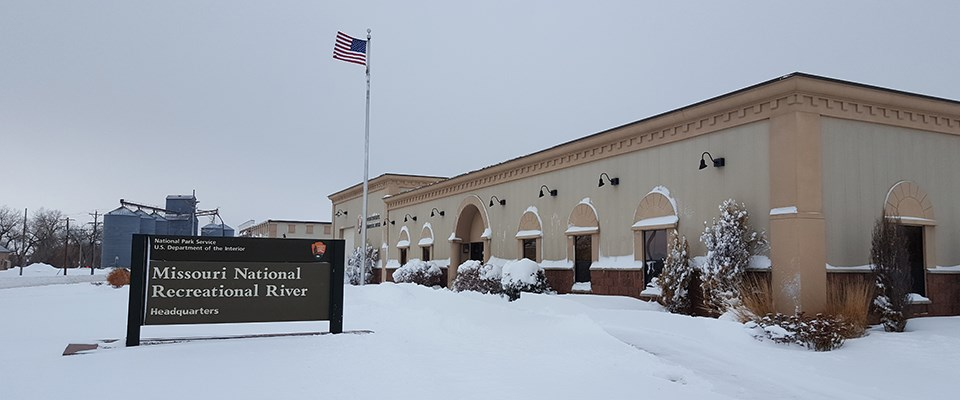 Outdoor winter scene of park headquarters building in snow. Sky above is gray.