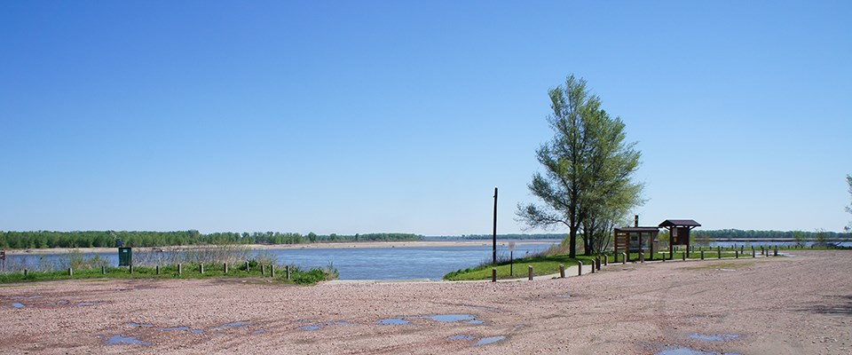 A flat gravel surface area with a single tree and utility pole stands in the scene. A river is in the background. Treeline makes the horizon.