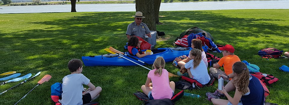 A National Park Service ranger talks to a group of kids about kayak use on the river.