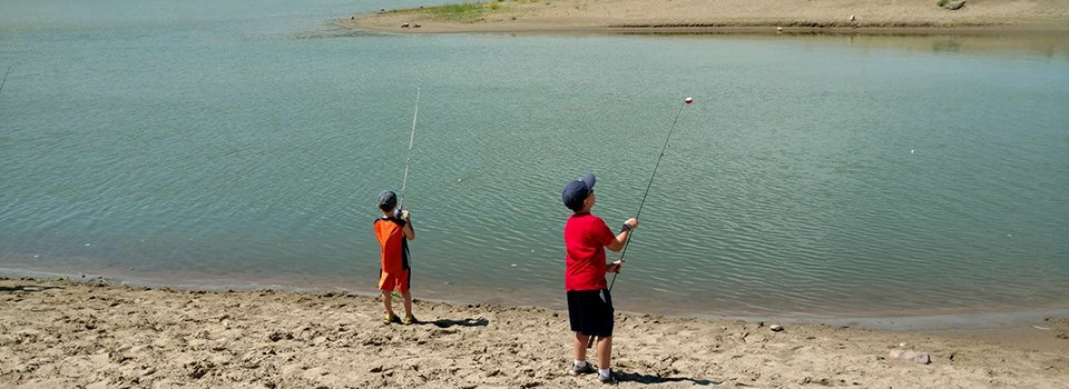 Two kids with their fishing poles are trying their luck with fishing the river.