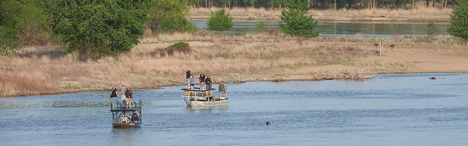 Anglers in boats bowfishing the river.