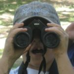 A camper looks through binoculars
