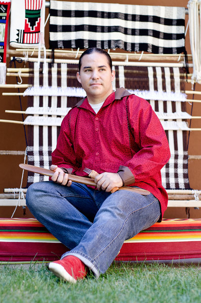 Louie Garcia sits in front of a traditional loom and weavings.