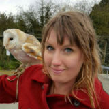 Woman with a barn owl perched on her shoulder.