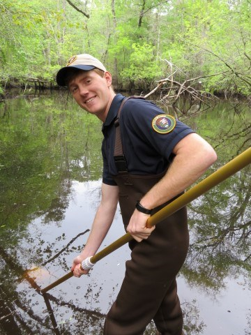 A uniformed park volunteer wearing waders stands in Moores Creek