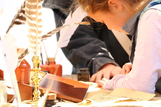 A Young Visitor tries her hand at Quill Pen Writing during a Living History Event
