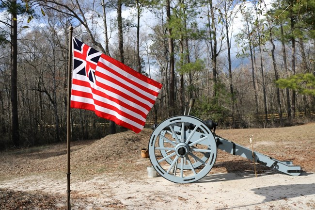 A Patriot Flag Flies in front of a Cannon at the site of the Battle of Moores Creek Bridge