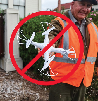 A man in a reflective vest is holding out a drone, and there is a red slash mark through it. No drones are allowed.