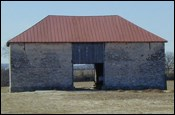 A stone barn with a red hipped roof.