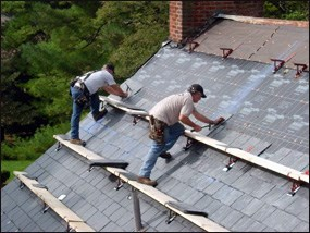 Workers install new slate roof on building.