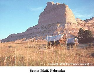 Photo image of Scotts bluff and emigrant wagons.