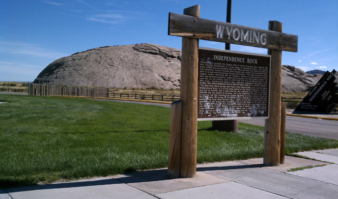 "A large wooden sign engraved with the words: ""Wyoming"" and ""Independence Rock"" and many words stands in front of a large rock buttress."