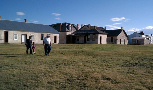 Two adults and one child walk across a grassy lawn in front of tan buildings with numerous chimneys. Small white clouds dot the sky.
