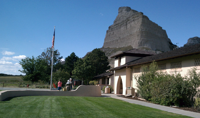 Visitors stand in front a large cream colored building with a green grass lawn and a large gray rock butte in the background.
