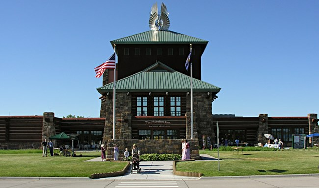 A large stone and wooden building stands above a green grassy lawn with numerous people walking around and a woman with a stroller.