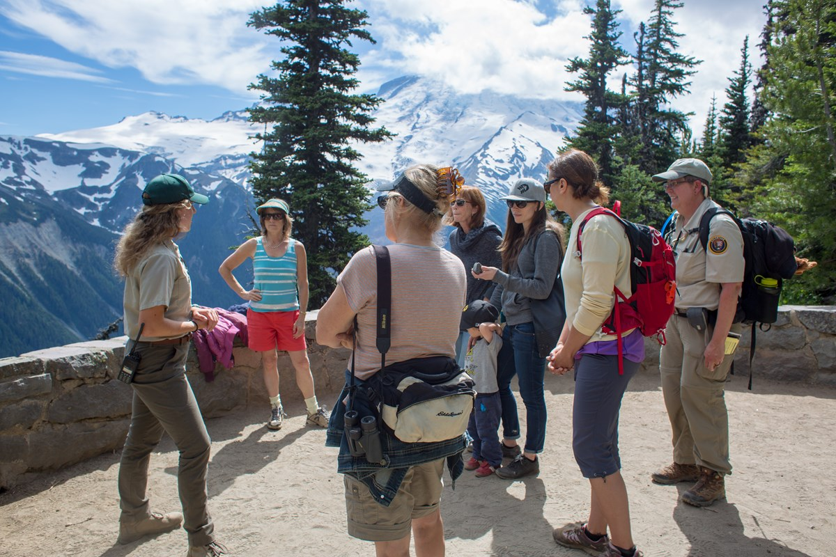A volunteer ranger talks to a group of visitors at a viewpoint in front of a mountain range.