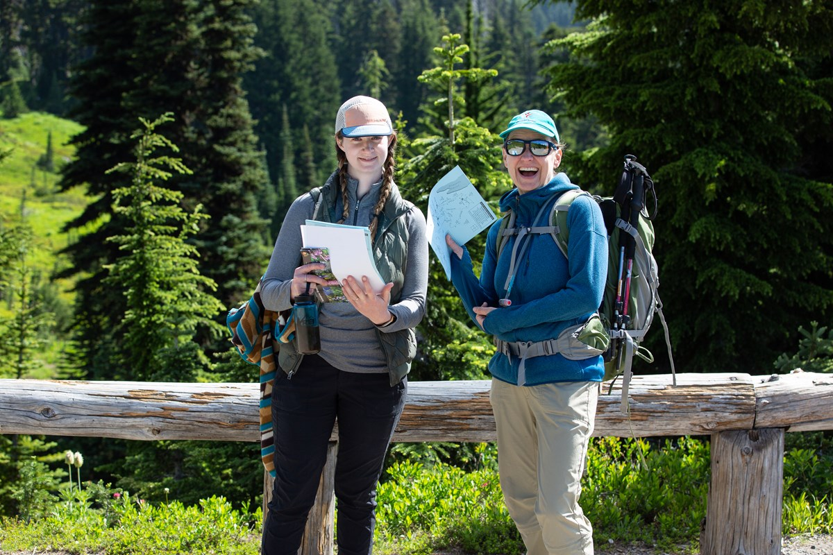 Two female volunteers pose on the trail with maps to hand out to visitors.