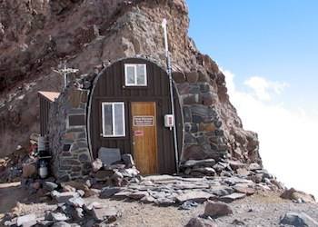 The stone ranger station of Camp Schurman, perched on a rocky ridge.
