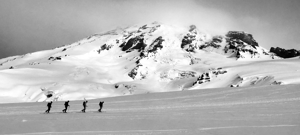 Four skiers cross a snowy slope on the side of Mount Rainier.