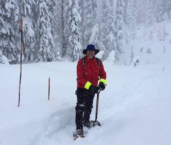 A man wearing snowshoes places snow poles to mark a snow covered trail.