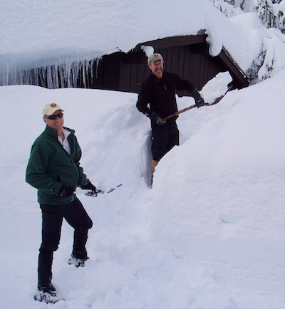 Two men shovel snow away from the entrance to a wood cabin.