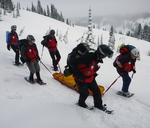 Five people in matching red winter jackets and on snowshoes pull a person wrapped in a yellow blanket on a toboggan across a snowy slope.