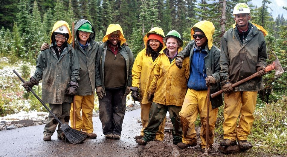 Group of volunteers in rain gear stand on the trail.