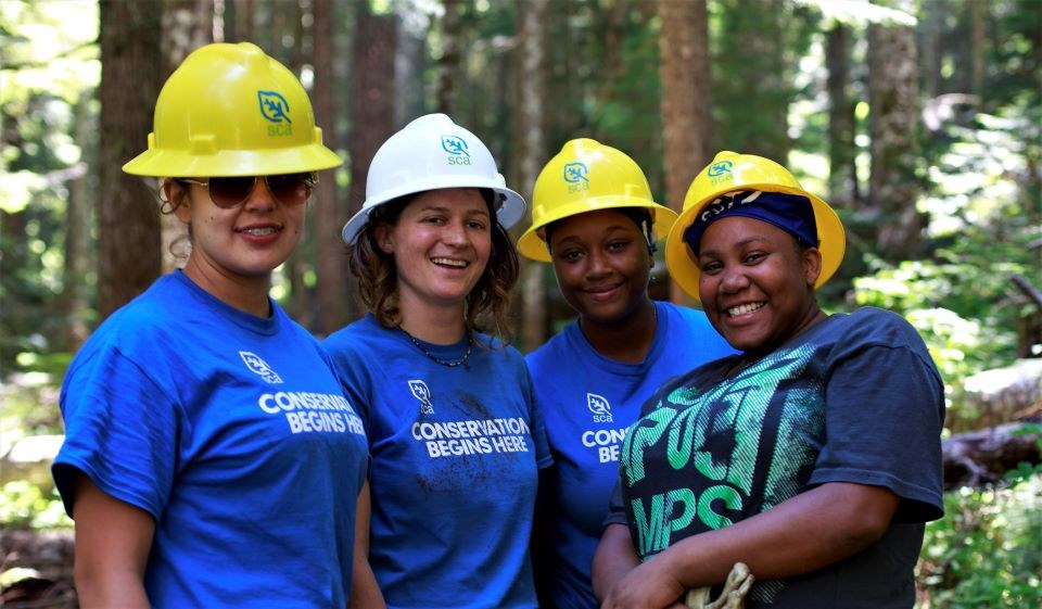 Four young adult volunteers in work gear smiling in the woods.