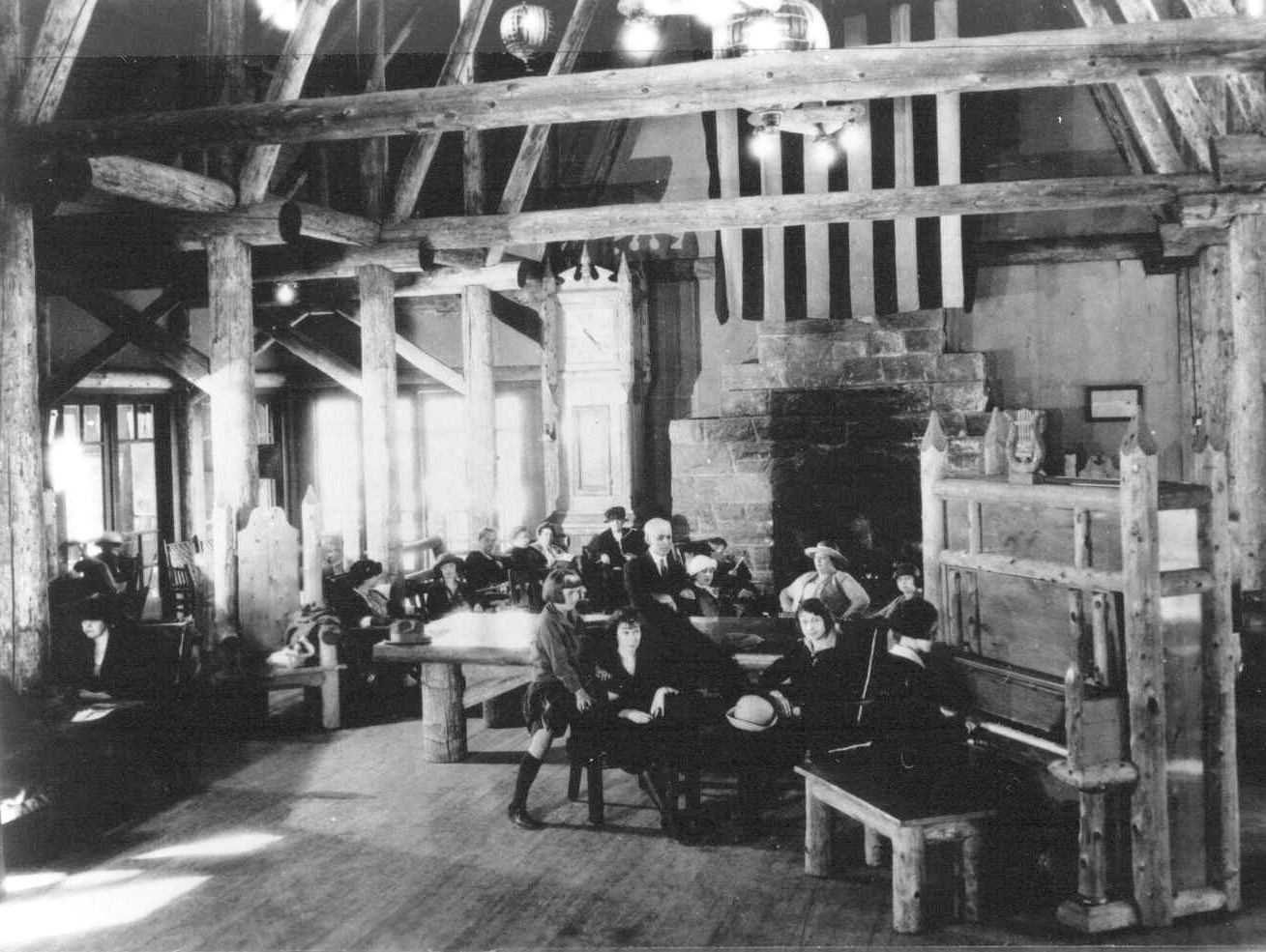 People seated near piano and fireplace in Paradise Inn in the 1920s.