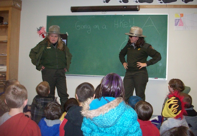 "Two rangers speak to a classroom of elementary school children. They stand in front of a chalkboard with the text ""Going for a Hike!"" written on it."
