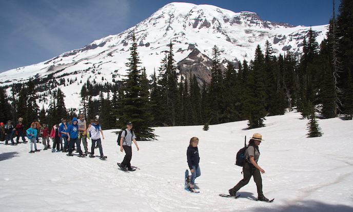 A ranger leads a group of students on snowshoes across a snow-covered meadow with views of Mount Rainier.