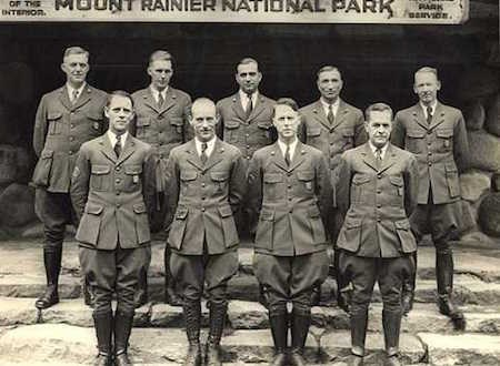 Black and white historic photo of two rows of park rangers in uniform.