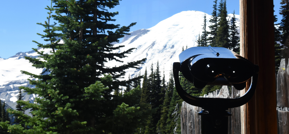 Spotting scope looks through a window at Mount Rainier.