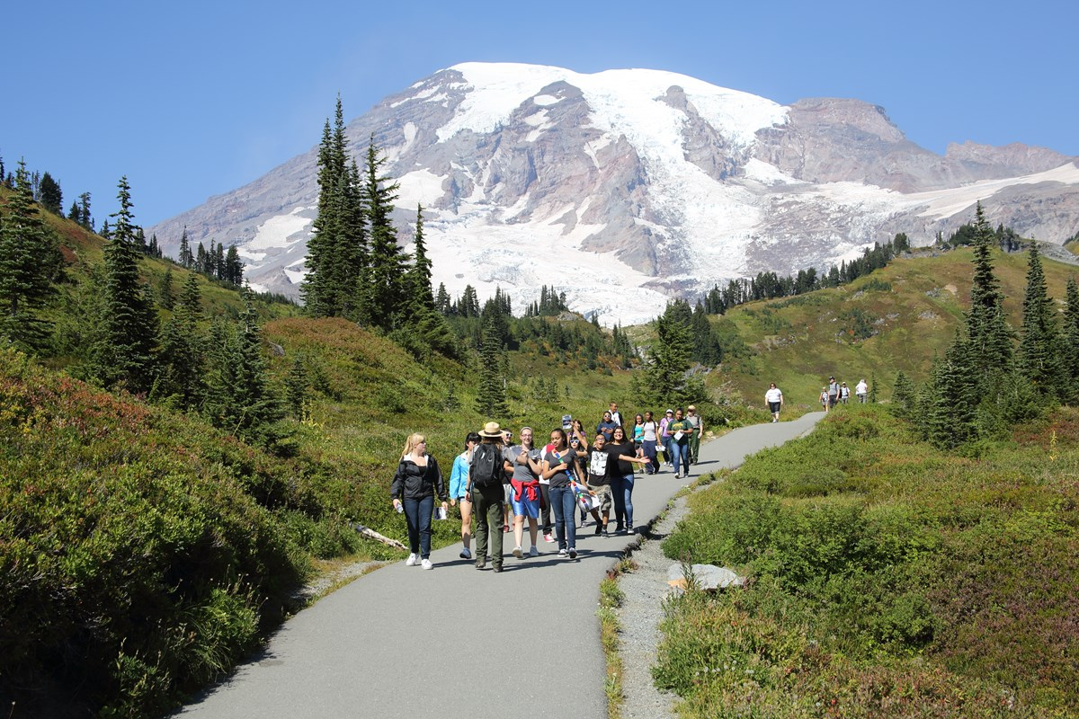 A ranger leading a group of students along a paved path with Mount Rainier in the background