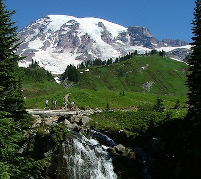 Hikers crossing a bridge over Myrtle Falls in front of Mount Rainier.